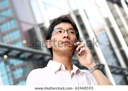 casual asian businessman talking on his cell phone.