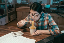 casual asian japanese woman blowing on hot instant noodles while eating with chopsticks sitting at wooden dining table in kitchen. hungry lady in midnight enjoy bedtime snack during over work time.