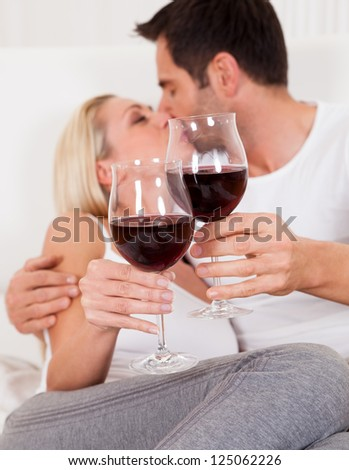 Casual attractive couple relaxing at home toasting each other with large glasses of red wine