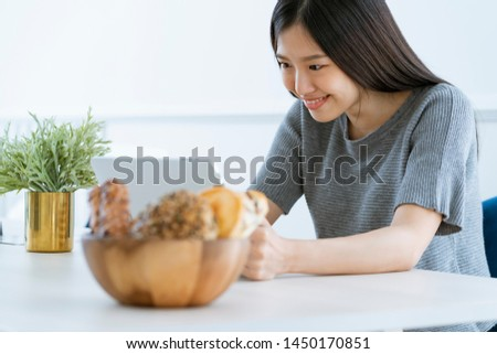 casual beautiful asian woman enjoy weekend morning withn tea and tablet white room interior background