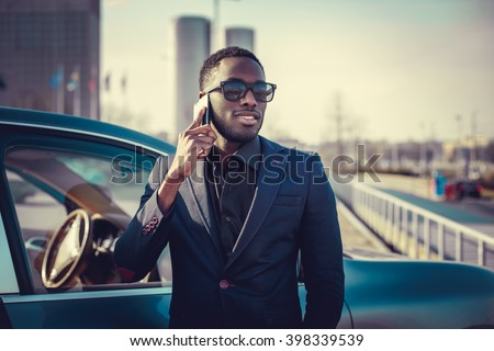 Casual black man in a suit talking by smartphone near a car.