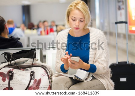 Casual blond young woman using her cell phone while waiting to board a plane at the departure gates