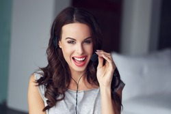 Casual brunette woman with headset, teeth smile, customer support from home, online job