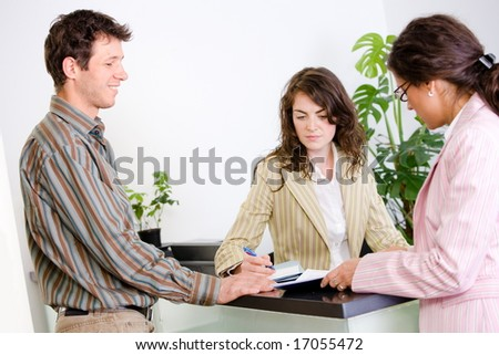 Casual business people working together at office reception, looking at documents, talking.