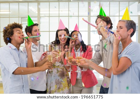 Casual business team celebrating with champagne and party horns in the office