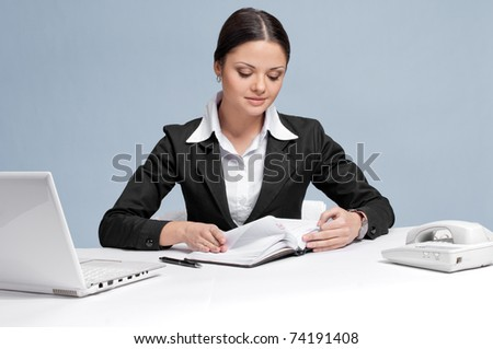 Casual business woman in office working with white table, laptop and diary personal organizer. Searching