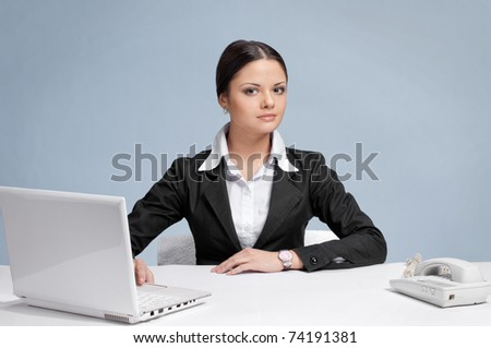 Casual business woman in office working with white table, laptop and phone