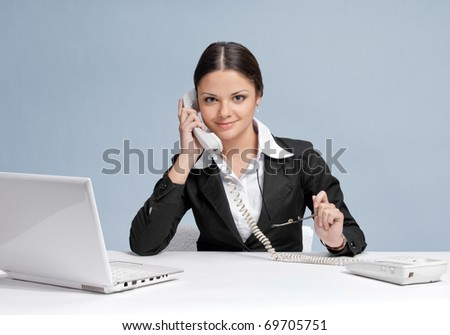 Casual business woman in office working with white table, laptop and talking by phone