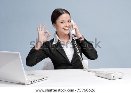 Casual business woman in office working with white table, laptop and talking by phone. Ok.
