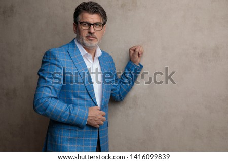 1dd88ca94 Casual businessman leaning against wall and adjusting his jacket's button  while wearing glasses and a blue