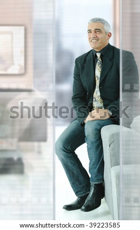 Casual businessman sitting on couch in modern office, smiling.