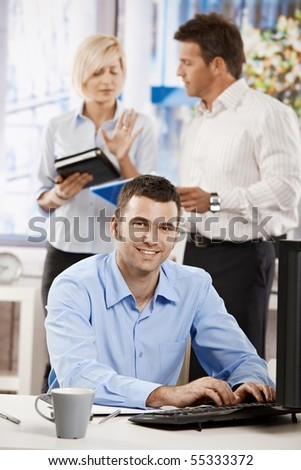 Casual businessman working with computer in office, looking at camera, smiling.