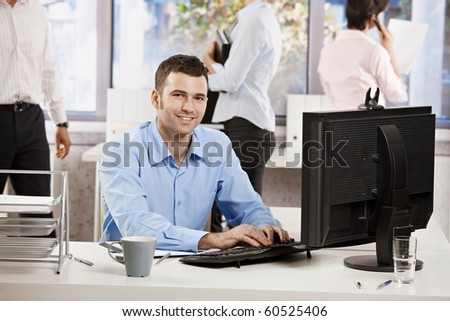 Casual businessman working with computer in office, looking at camera, smiling.?