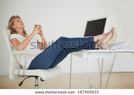 Casual businesswoman having a coffee with her feet up at desk in her office