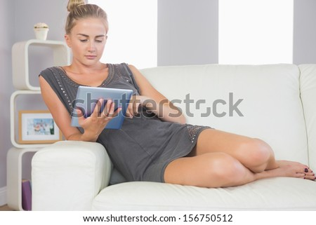Casual calm blonde relaxing on couch using tablet in bright living room