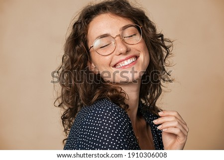 Casual cheerful woman with eyeglasses smiling at camera on cream background. Close up of happy young woman laughing with eyeglasses. Beautiful girl having fun with closed eyes showing a big grin. Foto stock ©