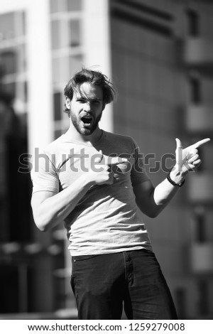 Casual concept. Excited man in casual wear pointing fingers in street. Casual in style. Casual fashion. Just look over there.