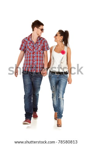 Casual couple is walking towards the camera  on White, looking at each other
