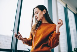 Casual dressed hipster girl in electronic headphones connecting to 4g wireless for listening online audio book, attractive woman with closed eyes dreaming about good life enjoying music podcast