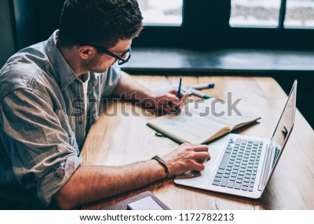 Casual dressed hipster guy writing organisation plan in textbook for education sitting at desktop with netbook,young man writing essay in notebook and preparing for academy test with modern technology