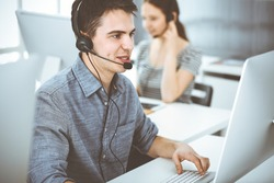Casual dressed young man using headset and computer while talking with customers online. Group of operators at work. Call center