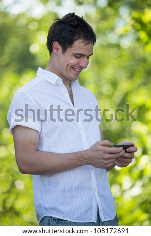 Casual Dressed Young Student Texting on Cell Phone Outdoor Smiling