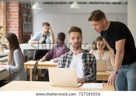 Casual entrepreneur explaining business project to his coworker. Two young employees discuss work-related goals in front of laptop at workplace in shared office. Team discussing marketing strategies.  #727181056