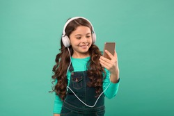 casual fashion for kids. kid long hair listen music in headset. small child make play list on smartphone. small girl use mp3 player. study in modern life. schoolgirl use digital device.