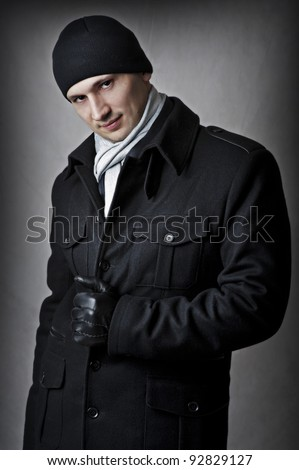 Casual. fashion portrait of sexy handsome man in black coat, hat, gloves and white scarf