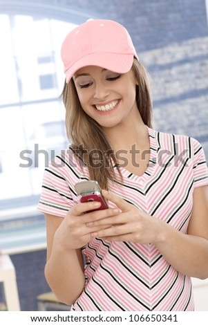 Casual girl in pink baseball cap using cellphone, smiling.
