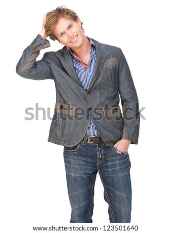 Casual guy with a smile on his face and his hand on his head. Isolated on white background. Male model has a friendly expression and wearing blue jeans and jacket. Isolated on white background