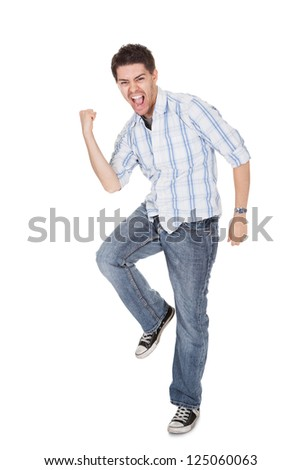Casual handsome young man in jeans shouting for joy raising his hands above his head