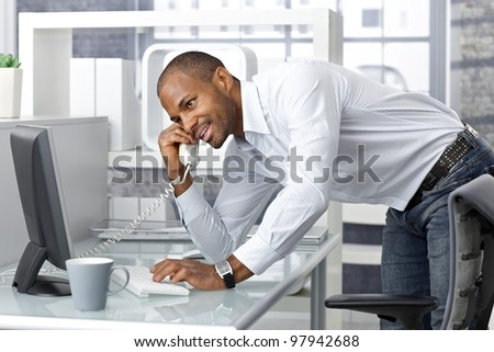 Casual happy businessman talking on landline phone in office, standing leaning on desk.