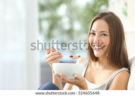 Casual happy woman dieting and eating cornflakes sitting on a couch at home