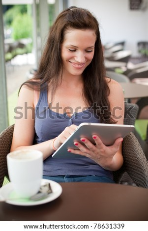 Casual happy young woman using her tablet in an open air cafe