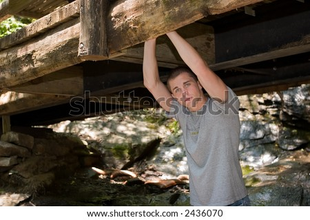 Casual high school senior portrait of a young man standing under a very rustic wooden bridge.