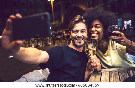Casual interracial couple drinking wine during date and taking a selfie in a terrace