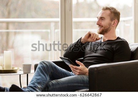 Casual laid back man wearing a black sweater and jeans, sitting down in a lounge chair indoors, holding a digital tablet.
