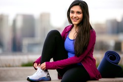 Casual lifestyle portrait of beautiful Indian American woman relaxing after cardio fitness exercise, city skyline buildings in background
