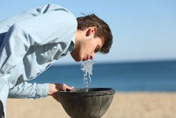 Casual man drinking water from a fountain on the beach