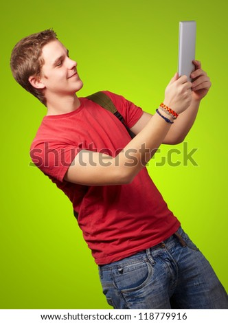 casual man holding digital tablet isolated on green background