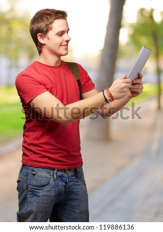 casual man holding digital tablet, outdoor