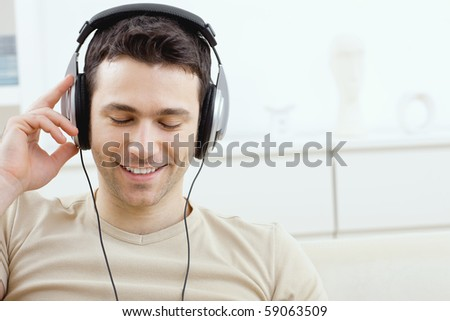 Casual man listening music with headphones at home, relaxing with closed eyes, smiling.