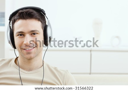 Casual man listening music with headphones at home, smiling.