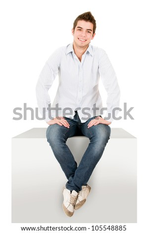 Casual man sitting on a cube - isolated over a white background