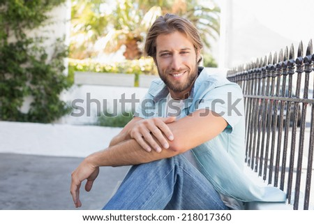 Casual man smiling at camera on a sunny day in the city