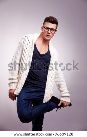 casual man standing on one leg isolated on gray background . fashion model wearing glasses and holding one of his legs