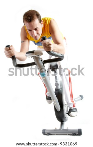 Casual man with sport clothes riding a static bike - stock photo