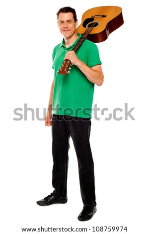 Casual music lover carrying guitar on his shoulders, full length portrait