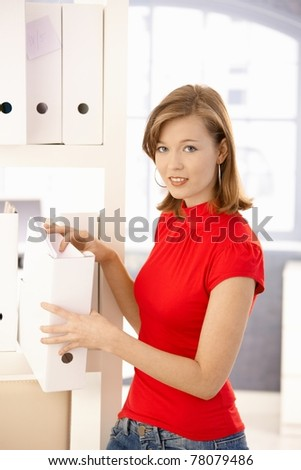Casual office worker organizing file folders in office.? - stock photo
